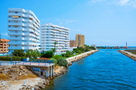 La Manga, Spain - July 29, 2021: A view of the Gola del Puerto canal in La Manga del Mar Menor, Murcia, Spain, connecting the lagoon and the Mediterranean sea, and the Estacio lighthouse on the right