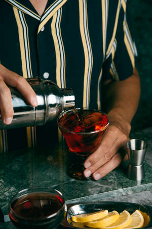 a young caucasian man, wearing a dark blue striped shirt, pours a red cocktail, from a metal shaker, in a glass placed on a green stone surface