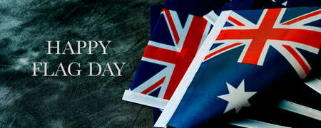 closeup of some australian flags and the text happy australia day on a dark gray background, in a panoramic format to use as web banner or header Banque d'images