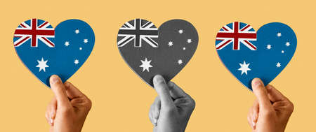 three australian flags in the shape of a heart, made with cutouts of paper of different colors, on a yellow background, in a panoramic format to use as web banner or header