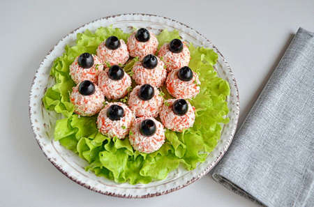 4. Place the balls on the lettuce leaves. Cut the olives into halves and put each half on a ball, press in a little. So the