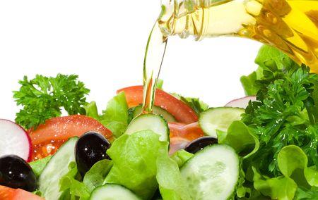 salade de légumes avec de l'huile d'olive versant d'une bouteille sur fond blanc