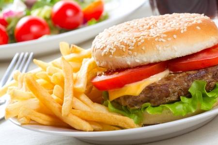 buns: hamburguesa con papas fritas y ensalada Foto de archivo