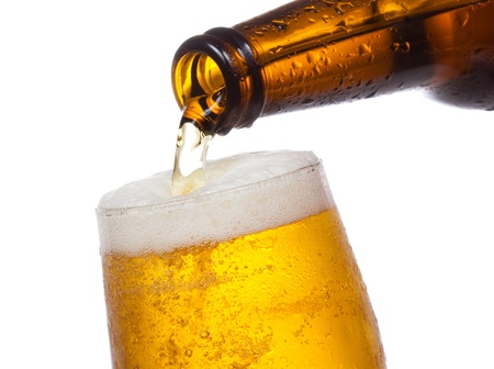 Beer pouring into glass on white background photo