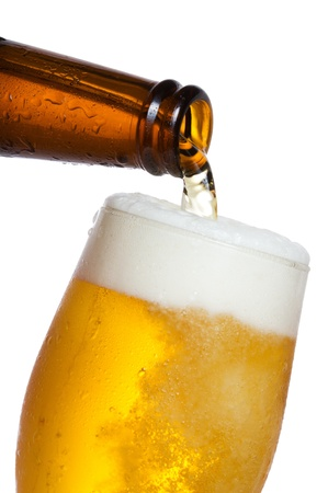 glass beer bottle: Beer pouring into glass on white background