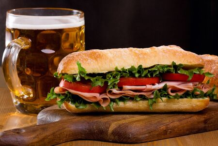 sandwich with bacon and vegetables with mug of beer