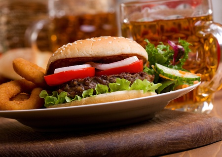 hamburger with vegetables and mug of beer photo