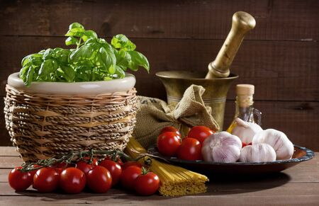 still life with pasta and fresh basil, tomatoes and garlic Stock Photo - 10832385