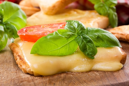 melted cheese: toast with melted cheese, tomato and basi Stock Photo