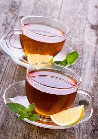 cups of tea with mint and lemon on wooden table Stock Photo - 11228538