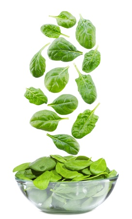 spinach leaves falling into bowl on white background Stock Photo