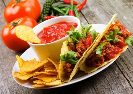 mexican food: plate with taco, nachos chips and tomato dip
