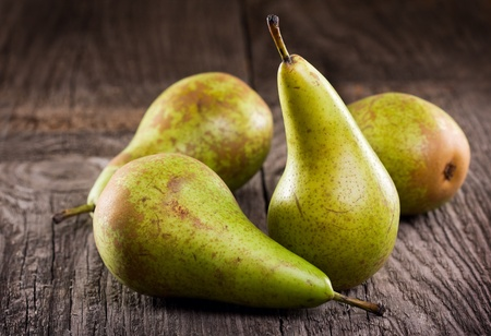 food still: green pears on wooden table