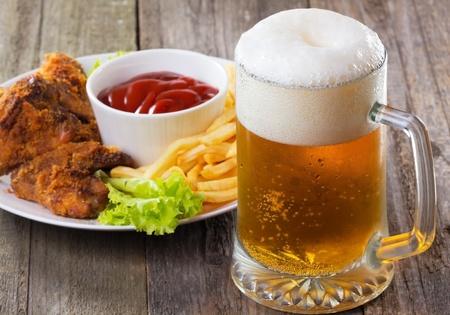 alitas de pollo: taza fr�a de cerveza con las alas de pollo Foto de archivo