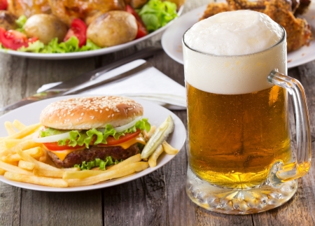 mug of beer with hamburger and fries Stock Photo