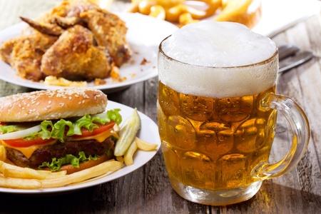 comida chatarra: jarra de cerveza con la hamburguesa y papas fritas Foto de archivo