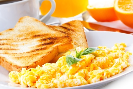 breakfast with scrambled eggs, toasts, juice and coffee photo