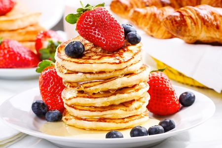 stack of pancakes with syrup, strawberry and blueberry photo