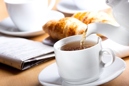 light breakfast: Pouring tea into cup of tea