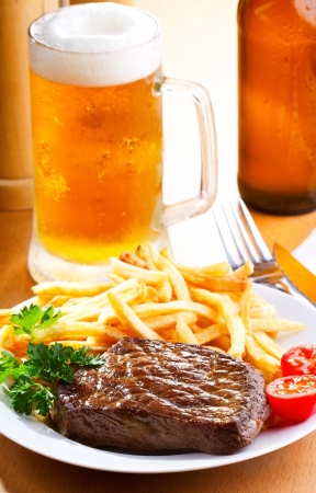 grilled steak with french fries and beer photo