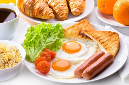 breakfast with fried eggs, sausages, cereal, toasts and coffee