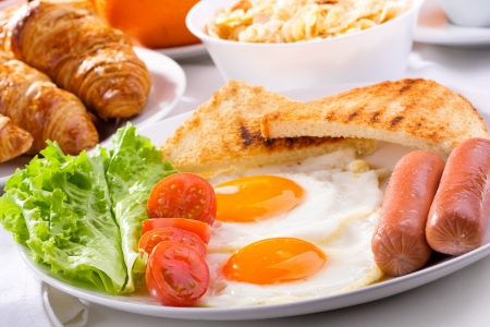 breakfast with fried eggs, sausages, tomatoes and toasts