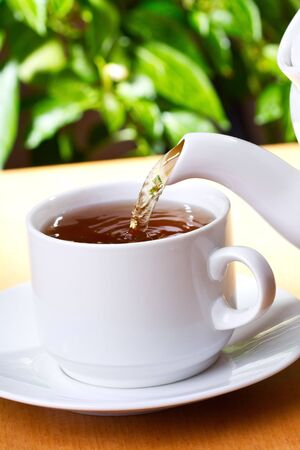 Pouring tea into cup of tea photo