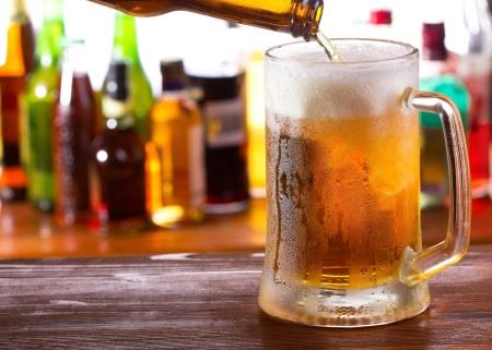 glass beer bottle: Beer pouring into mug