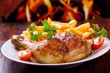 pollo a la plancha: muslo de pollo asado con patatas fritas y hierbas