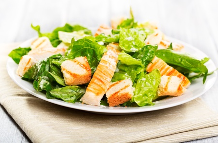 chicken salad: Caesar salad on wooden table