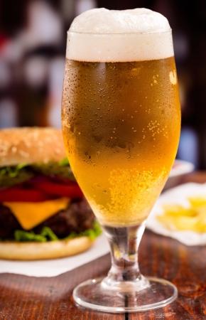 condensacion: vaso de cerveza y hamburguesa Foto de archivo