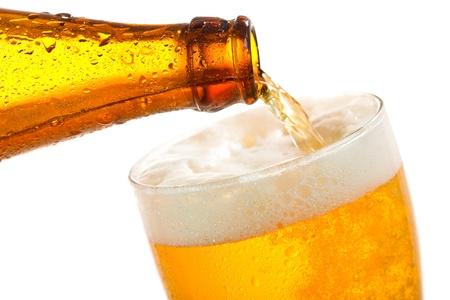 botellas de cerveza: Cerveza que vierte en el vidrio en un fondo blanco Foto de archivo
