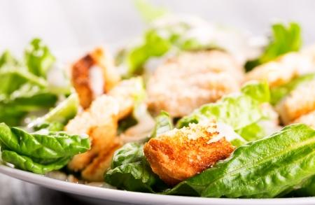 CHICKEN CAESAR SALAD: Caesar salad on wooden table