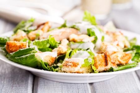 salad greens: Caesar salad on wooden table