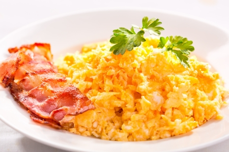 bacon and eggs: scrambled eggs with bacon and green basil