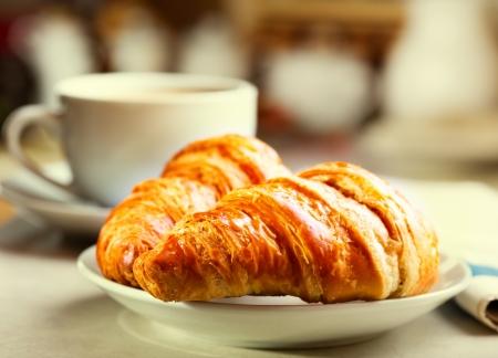 Frühstück mit Croissants, Tasse schwarzen Kaffee und Zeitung