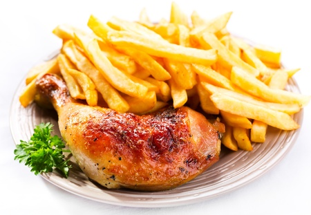 gebratenes Huhn Bein mit Pommes frites Kartoffeln auf einem Teller Lizenzfreie Bilder