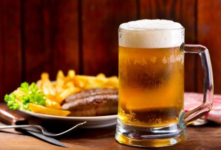 chorizos asados: taza de cerveza con plato de salchichas a la parrilla