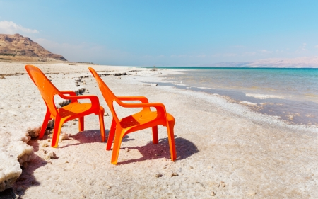 dead sea: two chairs on beach of dead sea