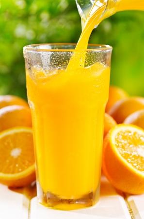Orangensaft gießt in glas Lizenzfreie Bilder