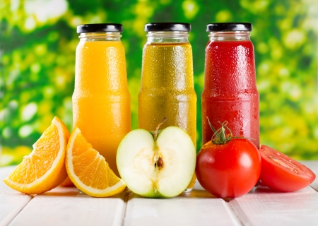 different bottles of juice with fruits on wooden table Foto de archivo