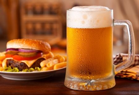 kalten Becher Bier und Hamburger Lizenzfreie Bilder