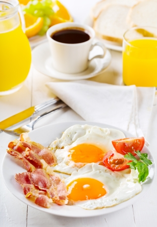 bacon and eggs: breakfast with fried eggs, toasts, juice, coffee and fruits