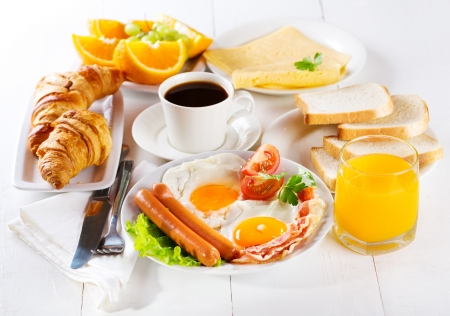 bacon and eggs: breakfast with fried eggs, croissants, juice, coffee and fruits