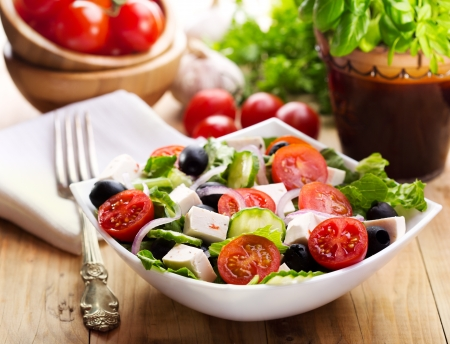 greek salad in a bowl on wooden table Stock Photo