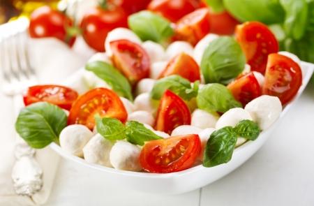 salade met mozzarella, tomaten en groene basilicum Stockfoto