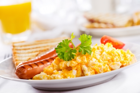 breakfast with scrambled eggs and sausages photo