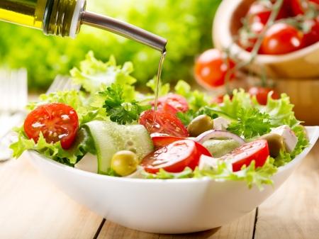 olijfolie gieten in bakje salade