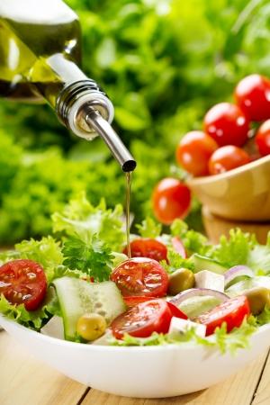 el aceite de oliva que vierte en un tazón de ensalada
