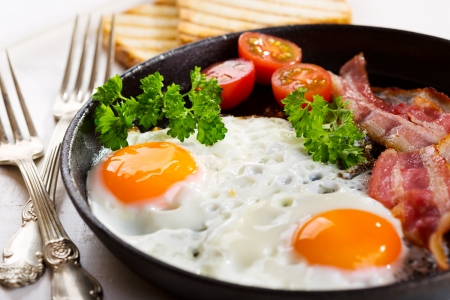 bacon and eggs: pan of fried eggs, bacon and vegetables on wooden table